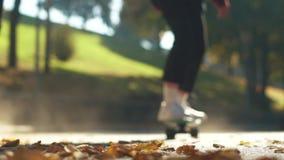 Os skateres montam um skate nas folhas caídas no parque Foco no primeiro plano Movimento lento filme