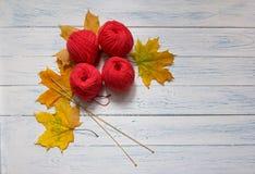 Os skeins vermelhos e as folhas amarelas caídas estão em uma tabela Foto de Stock Royalty Free