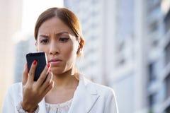 Os sms de datilografia tristes da mulher de negócio do retrato telefonam à rua Imagem de Stock