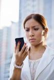 Os sms de datilografia tristes da mulher de negócio do retrato telefonam à rua Fotos de Stock