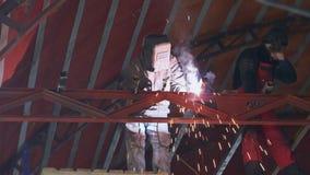 Os soldadores soldam uma construção enorme do metal no hangar vídeos de arquivo