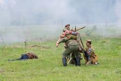 Os soldados ajudam um soldado ferido Fotos de Stock