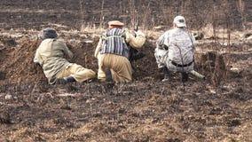 Os soldados com espingardas de assalto e uma bazuca sentam-se em uma trincheira nas hostilidades vídeos de arquivo