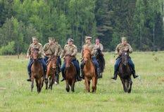 Os soldados da cavalaria montam em cavalos através do campo Fotografia de Stock