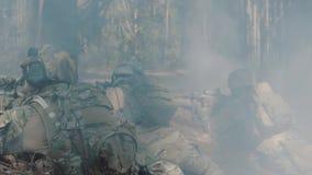 Os soldados estão lutando em uma trincheira em uma floresta fumarento video estoque