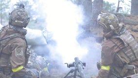 Os soldados na camuflagem com armas do combate fazem sua maneira fora da floresta, com o objetivo de capturá-la, as forças armada