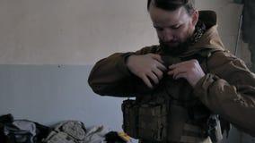 Os soldados na camuflagem preparam-se para a batalha e o equipamento e as armas da verificação para fora filme