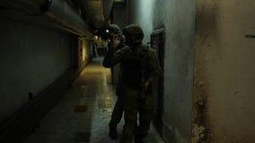 Os soldados totalmente equipadas que vestem o inimigo de ataque do uniforme da camuflagem, rifles aprontam-se para disparar Jogad filme