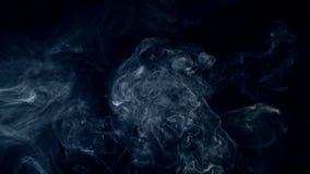 Os sopros da névoa, fumo, as nuvens abstratas brancas estão rodando lentamente contra o fundo escuro filme