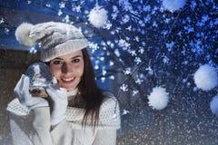 Os sorrisos bonitos da mulher e mostram seu Boule-de-neige fotografia de stock