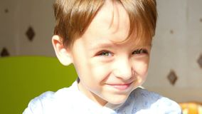 Os sorrisos e as piscadelas da criança um olho Emoções positivas reais de um menino dos anos de idade 3 em um movimento lento Luz video estoque
