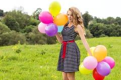 Os sorrisos louros novos bonitos da menina em um dia de verão andam com as bolas coloridas na cidade Fotografia de Stock Royalty Free