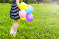 Os sorrisos louros novos bonitos da menina em um dia de verão andam com as bolas coloridas na cidade Fotos de Stock Royalty Free