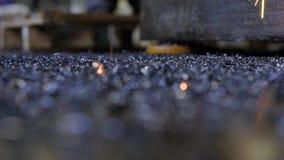 Os sparkles quentes da máquina de soldadura estão caindo em um assoalho sujo preto da oficina da planta metalúrgica, close-up filme