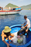 Os suplementos de transferência da terra aos barcos de pesca no mar de Nha Trang latem Imagens de Stock Royalty Free