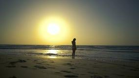 Os suportes bonitos da jovem mulher no Sandy Beach dourado olham o por do sol surpreendente, sonhos sobre o amor, pensam sobre o  video estoque