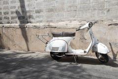 Os suportes clássicos brancos do 'trotinette' do Vespa estacionaram perto do concreto velho Fotografia de Stock Royalty Free