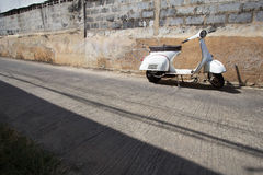 Os suportes clássicos brancos do 'trotinette' do Vespa estacionaram perto do concreto velho Imagem de Stock