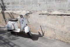 Os suportes clássicos brancos do 'trotinette' do Vespa estacionaram perto do concreto velho Imagem de Stock Royalty Free