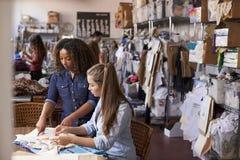 Os suportes da mulher para treinar um aprendiz na roupa projetam o estúdio fotografia de stock
