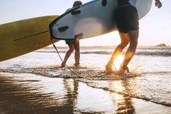 Os surfistas do filho e do pai correm em ondas de oceano com placas surfando imagens de stock