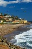 Os surfistas do papagaio entram na água ao longo da costa rochosa Foto de Stock Royalty Free