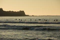 Os surfistas no final da noite expõem ao sol a espera de um grupo de ondas Imagem de Stock