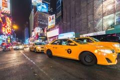 Os táxis de táxi amarelos e os sinais bondes de incandescência aproximam o Times Square Foto de Stock Royalty Free