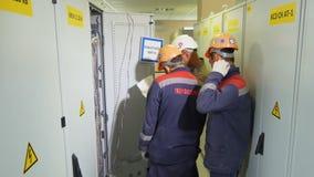 Os técnicos da vista lateral discutem o problema perto dos armários de poder da rede filme