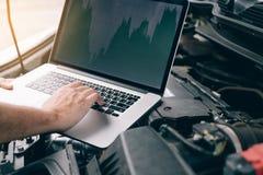 Os técnicos de reparo do carro usam laptop para medir valores do motor para a análise fotografia de stock