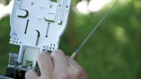 Os técnicos estão instalando a fibra ótica com cintas plásticas Fotografia de Stock Royalty Free