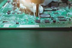 Os técnicos estão usando o ar quente que funde para parte na placa eletrônica imagens de stock royalty free