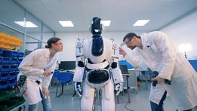 Os técnicos masculinos e fêmeas estão executando um procedimento de manutenção em um robô filme