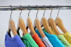 Os t-shirt de cores diferentes penduram na cremalheira de fechamento foto de stock