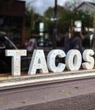 Os tacos assinam dentro da janela do restaurante imagem de stock royalty free