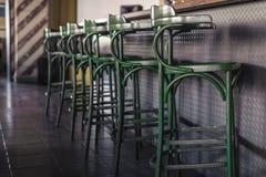 Os tamboretes de barra verdes do vintage estão em seguido ao lado do contador da barra Quadro horizontal fotos de stock