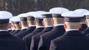 Os tampões brancos são vestidos para soldados, estão na linha e olham o comandante video estoque
