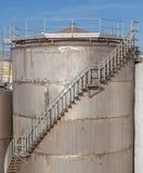 Os tanques de óleo enormes da gasolina com as escadas exteriores na refinaria indus Fotos de Stock