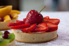 Os tartlets apetitosos com morango e vários berrys e frutos estão encontrando-se em uma toalha de mesa branca fotografia de stock