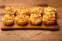 Os Tartlets cozeram com batata, queijo, o presunto e salsa triturados Fotos de Stock Royalty Free