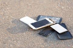Os telefones celulares quebrados estão no asfalto Fotos de Stock