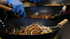 Os tenazes de brasa tomam vegetais, carne, massa, das bandejas e põem-nas em uns sacos de papel vídeos de arquivo