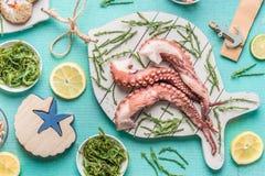 Os tentáculos do polvo serviram na placa de corte branca na forma dos peixes com salada das algas em umas bacias na luz - fundo a imagens de stock royalty free