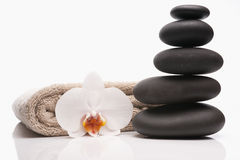 Os termas apedrejam a toalha e a orquídea Imagens de Stock Royalty Free