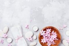 Os termas, aromaterapia, fundo da beleza com seixo da massagem, perfumaram flores molham e velas na opinião de tampo da mesa de p Fotografia de Stock