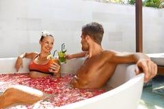 Os termas relaxam Pares no amor em bebidas bebendo do banho da flor imagens de stock royalty free