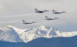 Os Thunderbirds da força aérea voam sobre rochoso tampado neve Imagem de Stock