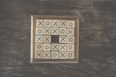 os tic-TAC-teen spel door houtsnede op houten lijst wordt gemaakt die Educatio Royalty-vrije Stock Fotografie
