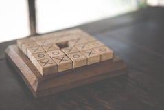 os tic-TAC-teen spel door houtsnede op houten lijst wordt gemaakt die Educatio Stock Afbeeldingen
