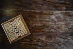 os tic-TAC-teen spel door houtsnede op houten lijst wordt gemaakt die Educatio Stock Foto